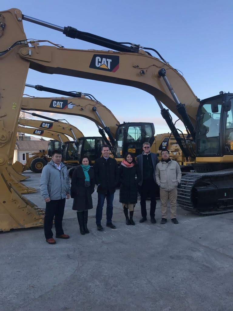 6 people standing at an excavator