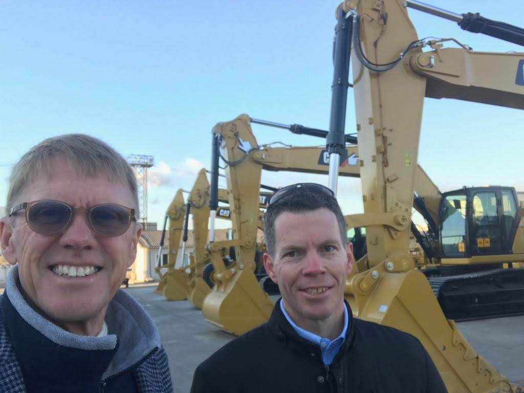 2 men taking a selfie with some excavators.
